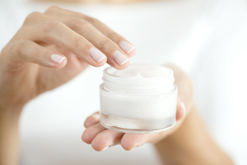 Female hand holding moisturizer in hand, vertical