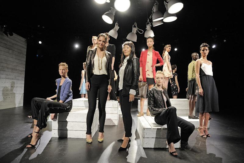In this photo provided by Holmes & Yang,  Katie Holmes, center left, and Jeanne Yang, center right, pose for a portrait in front of the Holmes & Yang Spring 2013 collection during Fashion Week in New York, Tuesday, Sept. 11, 2012. (AP Photo/Holmes & Yang, Dan Ashby)
