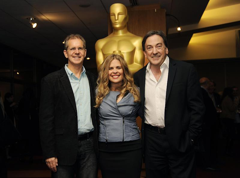 """Chris Buck, left, and Jennifer Lee, center, co-directors of the Oscar-nominated animated feature film """"Frozen,"""" pose with producer Peter Del Vecho at a reception featuring the Oscar nominees in the Animated Feature Film category on Friday, Feb. 28, 2014, in Beverly Hills, Calif. The 86th Oscars ceremony will be held on Sunday at the Dolby Theatre in Los Angeles. (Photo by Chris Pizzello/Invision/AP)"""