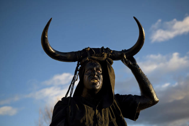 <p>A man covered in oil and soot carrying the horns of a bull on his head and cowbells on a belt (representing the devil) pauses during carnival celebrations in the village of Luzon, Spain, Feb. 9, 2013. (Photo: Daniel Ochoa de Olza/AP) </p>