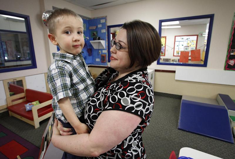 In this April 4, 2012, photo, Kelly Andrus holds her son Bradley in his classroom at Children's Choice Learning Centers Inc., in Lewisville, Texas. Bradley, who turns three in a couple of weeks, was diagnosed a year ago with mild autism.  For the first time in nearly two decades, experts want to rewrite the definition of autism. Some parents fear that if it's narrowed and their kids lose the label, they may also lose out on special therapist. (AP Photo/Tony Gutierrez)
