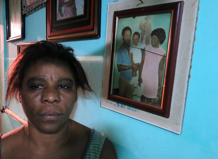"""In this Oct. 1, 2013 photo, Amarildo de Souza's sister, Maria Lacerda, poses for a photo next to a family portrait that shows her missing brother, Amarildo, as an infant, held by their parents, Joao and Carmen, at the Rocinha slum, in Rio de Janeiro, Brazil. De Souza disappeared in July after last being seen in police custody in Rocinha slum. Investigators said they've recommended to prosecutors that 10 police officers from the slum's """"pacifying"""" unit be charged with de Souza's abduction, torture, death and disappearance of his body. (AP Photo/Bradley Brooks)"""
