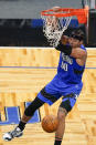 Orlando Magic forward Aaron Gordon (00) hangs from the rim after dunking against the Brooklyn Nets during the second half of an NBA basketball game, Friday, March 19, 2021, in Orlando, Fla. (AP Photo/John Raoux)