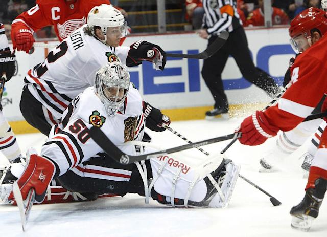 Detroit Red Wings center Gustav Nyquist, of Sweden, right, scores against Chicago Blackhawks goalie Corey Crawford (50) in the second period of an NHL hockey game Wednesday, Jan. 22, 2014, in Detroit. (AP Photo/Paul Sancya)