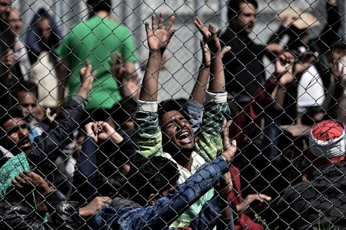 A man holds his hands up behind a chain link fence as Pakistani and Afghan migrants protest inside the Moria detention center in Mytilene on the Greek island of Lesbos on April 5, 2016 against deportation to Turkey (AFP Photo/Aris Messinis)
