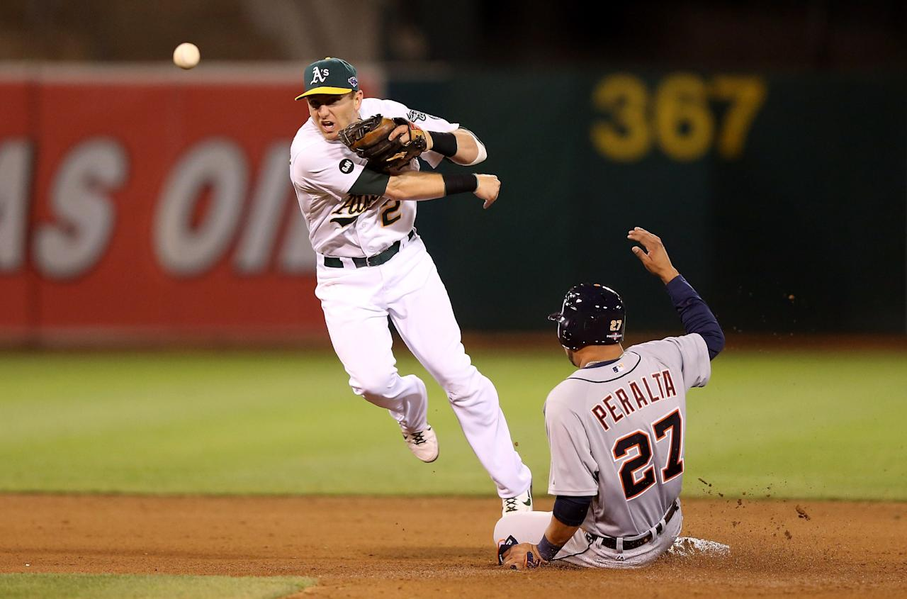 OAKLAND, CA - OCTOBER 09: Jhonny Peralta #27 of the Detroit Tigers slides into second base and is out as Cliff Pennington #2 of the Oakland Athletics throws to first base trying to turn a double play in the fifth inning during Game Three of the American League Division Series at Oakland-Alameda County Coliseum on October 9, 2012 in Oakland, California.  (Photo by Ezra Shaw/Getty Images)