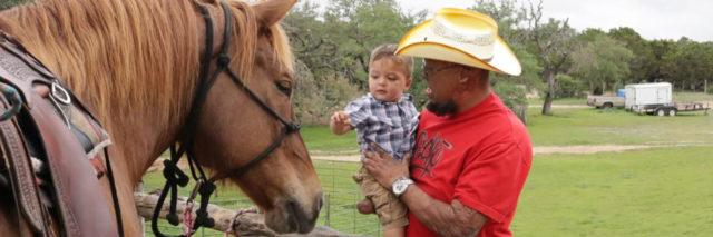 Burn survivor introducing his child to a horse.