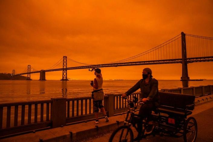 Amy Scott of San Francisco takes in the view from the Embarcadero as smoke from various wildfires burning across Northern California mixes with the marine layer, blanketing San Francisco in darkness and an orange glow on September 9, 2020 in San Francisco, California. (Photo by Philip Pacheco/Getty Images)