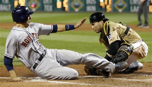 Houston Astros' Jason Castro, left, scores from third on a ground ball by Matt Dominguez as Pittsburgh Pirates catcher Russell Martin, right, tries to tag him in the 11th inning of a baseball game on Saturday, May 18, 2013, in Pittsburgh. The Astros won 5-4 in eleven innings. (AP Photo/Keith Srakocic)