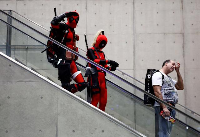 A man and woman in Deadpool costumes ride an escalator as they enter the venue of Tokyo Comic Con at Makuhari Messe in Chiba, Japan December 1, 2017. REUTERS/Kim Kyung-Hoon