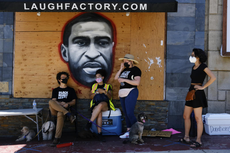 Volunteers wearing masks to protect from the coronavirus stand in front of a portrait of George Floyd painted on the side of the comedy club The Laugh Factory during the unveiling of a 148-foot tribute mural to Black Lives Matter in Los Angeles on Tuesday, July 7, 2020. The artwork was created by five African American artists, Alexandra Allie Belisle, Amanda Ferrell Hale, Noah Humes, PeQue Brown, and Shplinton. Said to be the largest in the nation the mural was commissioned by Los Angeles Fourth District Councilmember David Ryu and the Laugh Factory. (AP Photo/Richard Vogel)