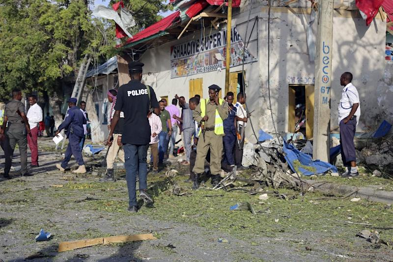 Local residents and Somali soldiers stand at site of a car bomb attack in the center of Mogadishu on September 11, 2017