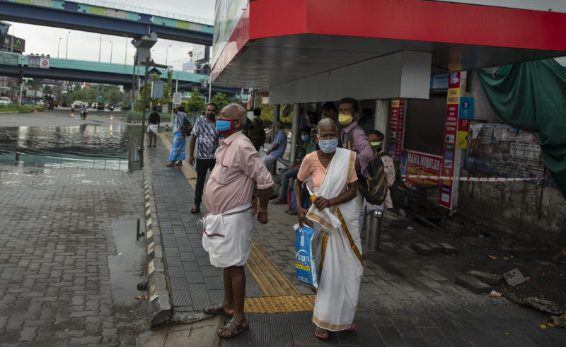 People wearing face masks to protect from the new coronavirus as they wait for bus transport in Kochi, Kerala state, India, Monday, June 1, 2020. More states opened up and crowds of commuters trickled on the roads in many cities as India's three-phase plan to lift the virus lockdown kick started Monday amidst an upward trend in new infections and fatalities due to COVID-19. (AP Photo/ R S Iyer)