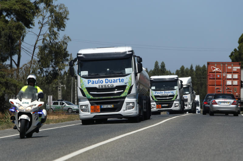 Police escorts a convoy of tanker trucks leaving a fuel depot in Aveiras, outside Lisbon, Tuesday, Aug. 13, 2019. Soldiers and police officers are driving tanker trucks to distribute gas in Portugal as an open-ended truckers' strike over pay enters its second day. The government has issued an order allowing the army to be used. (AP Photo/Armando Franca)