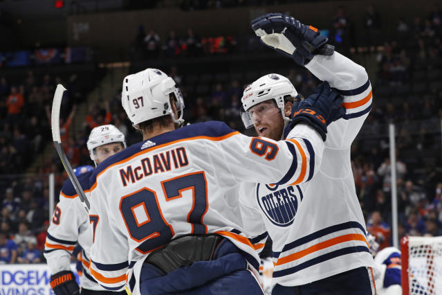 Edmonton Oilers left wing James Neal, right, celebrates with center Connor McDavid (97) after scoring a goal during the first period of the team's NHL hockey game against the New York Islanders, Tuesday, Oct. 8, 2019, in Uniondale, N.Y. Oilers center Leon Draisaitl is at back left. (AP Photo/Kathy Willens)