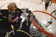 Phoenix Suns' Deandre Ayton (22) attempts a shot ahead of Milwaukee Bucks' Brook Lopez (11) during the first half of Game 1 of basketball's NBA Finals, Tuesday, July 6, 2021, in Phoenix. (Christian Petersen/Pool Photo via AP)