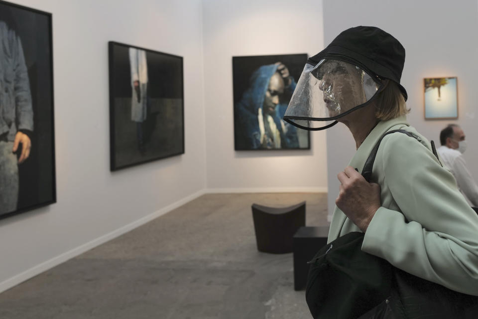 A visitor, wearing a protective face mask as a precaution against the coronavirus, looks on during the private view of Art Paris at the Grand Palais in Paris, Wednesday Sept. 9, 2020. Fears and restrictions over the coronavirus have caused the cancellation of all of 2020's premiere global art fairs, such as Art Basel, Frieze London, and Art Basel in Miami Beach, stymieing the main commercial artery of the multi-million-dollar industry.But organizers of Art Paris, France's second biggest contemporary art fair, have thrown caution to the wind, and are opening their doors to thousands of visitors from Thursday in the Grand Palais for a four-day show. (AP Photo/Francois Mori)