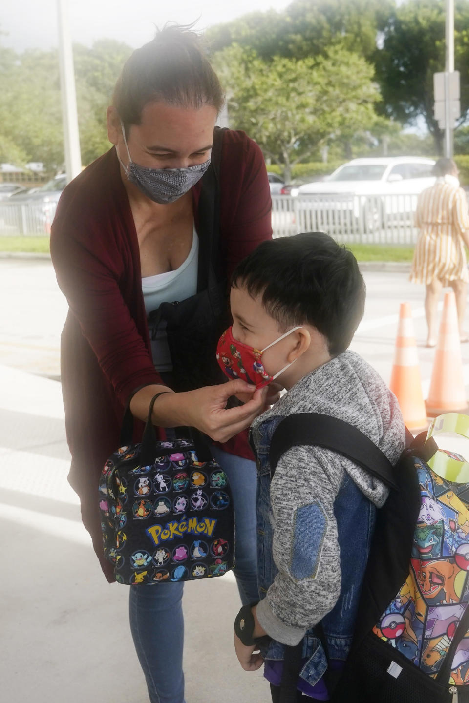 Cynthia Fernandez adjusts the facemark on her son Dael Fernandez, during his first day at Dolphin Bay Elementary School, Wednesday, Aug. 18, 2021, in Miramar, Fla. Broward County School board requires that masks be worn at all public schools. (AP Photo/Marta Lavandier)