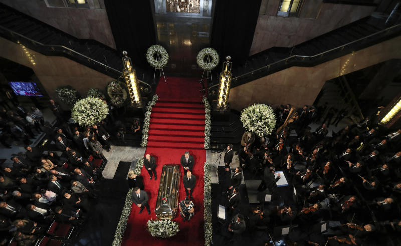 People stand next to the casket containing the remains of Mexican crooner Jose Jose during a homage at the Palace of Fine Arts in Mexico City, Wednesday, Oct. 9, 2019. Jose Jose died Sept. 28 in South Florida. His body was cremated in Miami and it was agreed after a dispute among relatives that half the ashes would remain there and the other half would be brought to Mexico. (AP Photo/Fernando Llano)