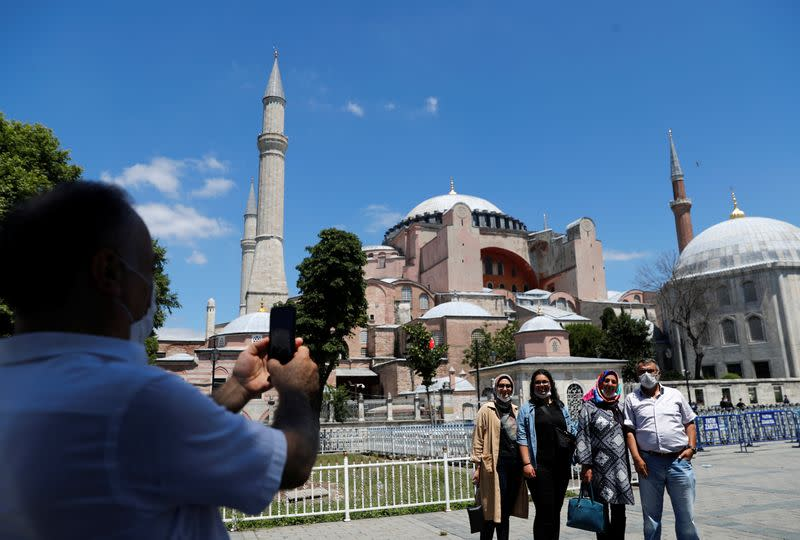 People pose for a picture in front of Hagia Sophia, or Ayasofya-i Kebir Camii, in Istanbul