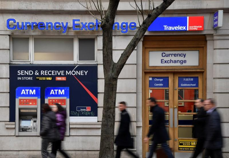 People walk past a branch of Travelex Currency Exchange in London