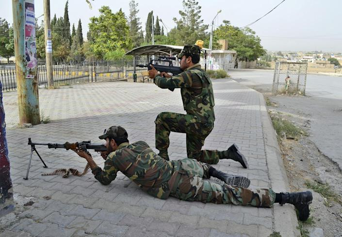 Pakistani security forces take up positions outside a hospital during a gun battle in Quetta, Pakistan, Saturday, June 15, 2013. Gunmen took over parts of a hospital in southwestern Pakistan Saturday after a bomb went off inside its emergency room, officials said. Several people died before authorities stormed the building and freed the hostages trapped inside. (AP Photo/Arshad Butt)