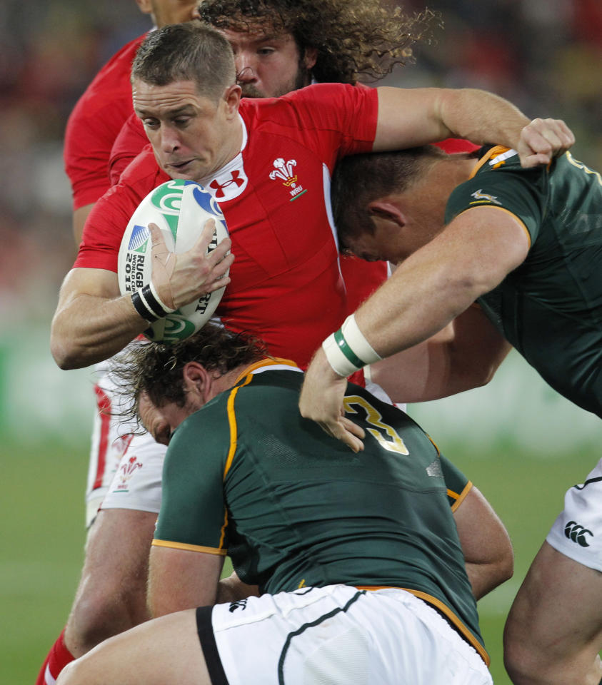 Wales Shane Williams is tackled by South Africa's John Smit and Jannie Du Plessis during their Rugby World Cup game at the Wellington Regional Stadium in Wellington, New Zealand, Sunday, Sept. 11, 2011. (AP Photo/Christophe Ena)