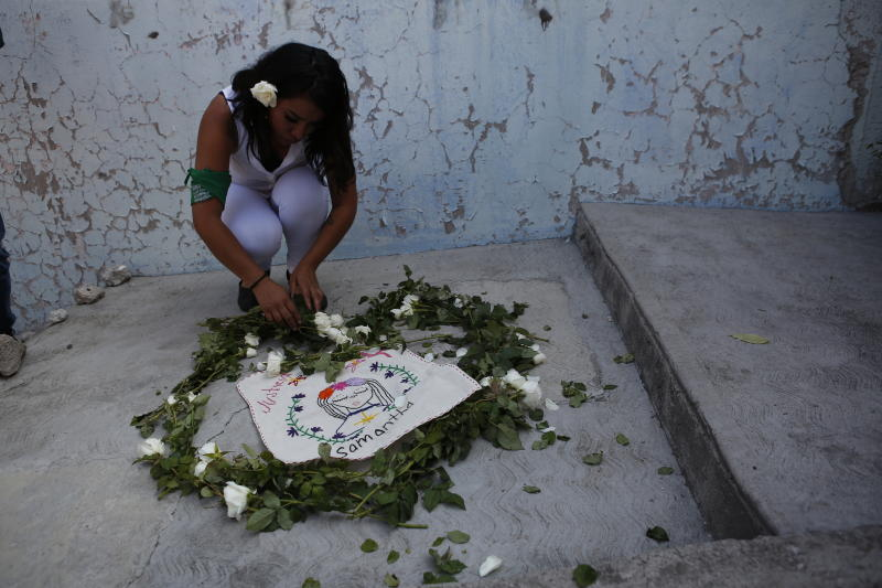 """An activist from the """"Women from the Periphery for the Periphery Collective"""" places flowers where the body of 2-year-old Samantha was found dead outside her home in June, during a caravan to protest femicide in Ecatepec, Mexico, Sunday, Oct. 6, 2019. The collective of activists and the relatives of murdered females visited four sites where females were found dead in Ecatepec, in the state of Mexico where authorities declared in 2015 an alert concerning gender violence against women. (AP Photo/Ginnette Riquelme)"""
