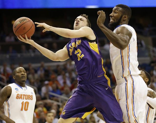 Albany guard Peter Hooley (12) drives to the basket as Florida center Patric Young (4) defends during the first half of a second-round game in the NCAA college basketball tournament on Thursday, March 20, 2014, in Orlando, Fla. (AP Photo/John Raoux)
