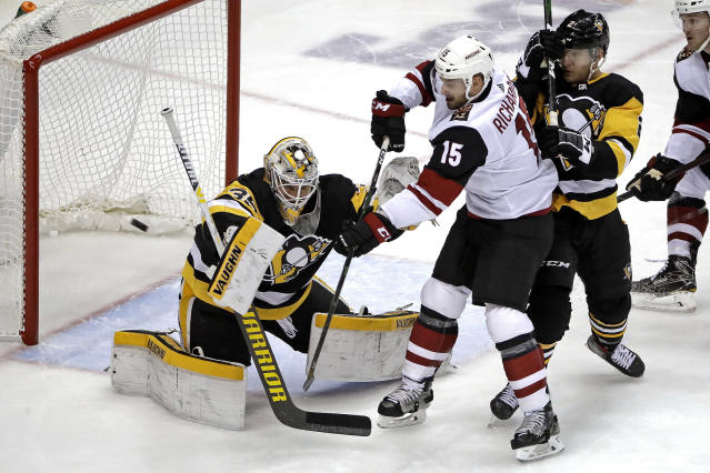 Pittsburgh Penguins goaltender Tristan Jarry (35) blocks a shot deflected by Arizona Coyotes' Brad Richardson (15) with Penguins' Chad Ruhwedel defending during the first period of an NHL hockey game in Pittsburgh, Friday, Dec. 6, 2019. (AP Photo/Gene J. Puskar)