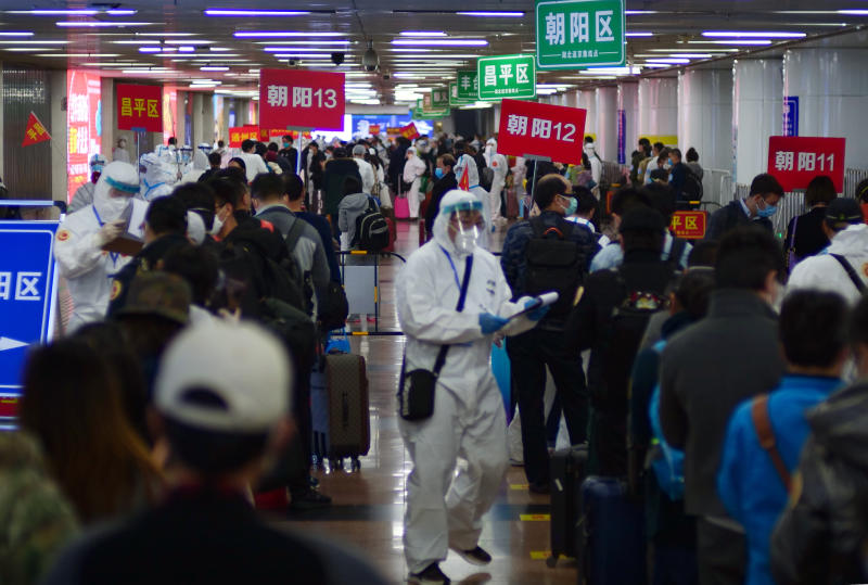 Passengers from Wuhan stand in lines designating where they will quarantine in Beijing, China, on Wednesday, April 15, 2020. Wuhan, the city at the center of the global coronavirus epidemic, lifted a 76-day lockdown and allowed people to leave for destinations across China. (AP Photo/Sam McNeil)
