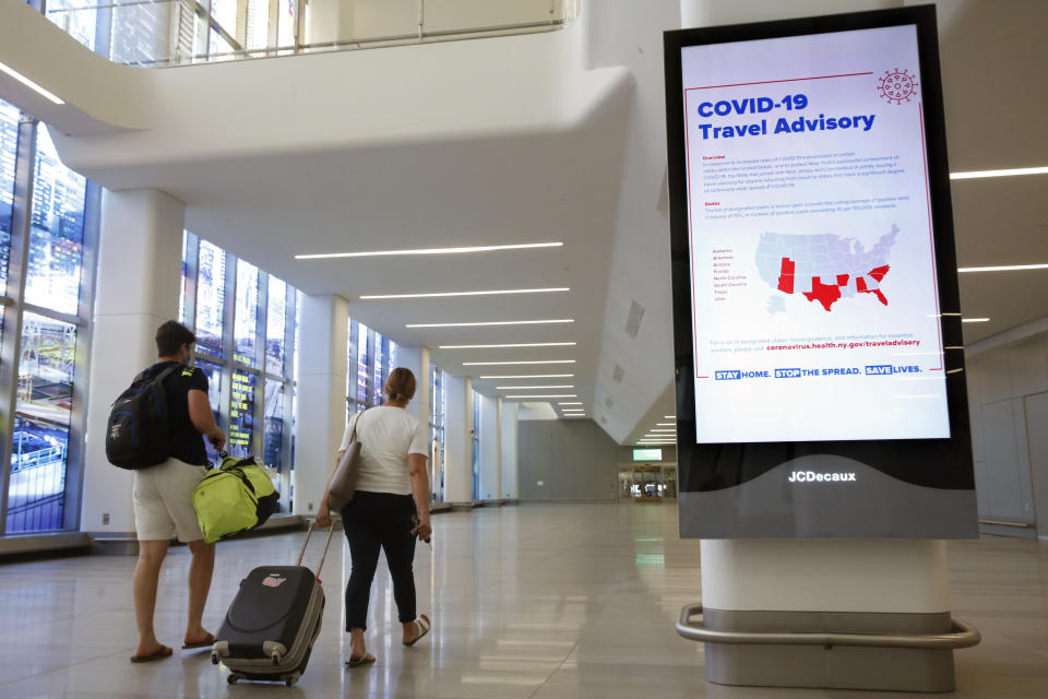 """Arriving travelers walk by a sign in the baggage claim area of Terminal B at LaGuardia Airport, Thursday, June 25, 2020, in New York. New York, Connecticut and New Jersey are asking visitors from states with high coronavirus infection rates to quarantine for 14 days. The """"travel advisory"""" affects three adjacent Northeastern states that managed to check the spread of the virus this spring as New York City became a hot spot. Travelers from mostly southern and southwestern states including Florida, Texas Arizona and Utah will be affected starting Thursday. The two-week quarantine will last two weeks from the time of last contact within the identified state. (AP Photo/Kathy Willens)"""