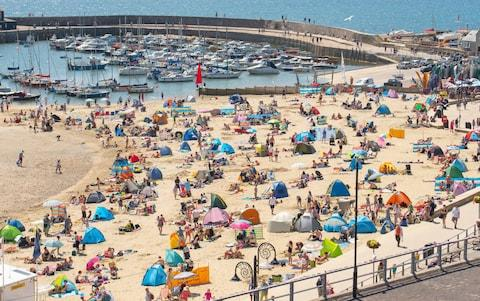 Holidaymakers and day trippers pack the beach at Lyme Regis in Dorset - Credit: Celia McMahon/Alamy Live News