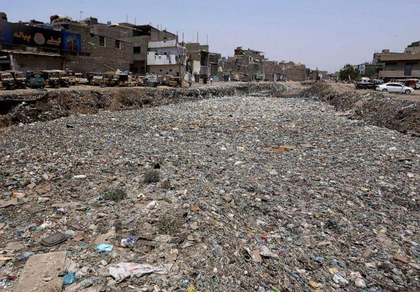 PHOTO: Thick layers of garbage float over a drainage area at a neighborhood in Karachi, Pakistan, April 23, 2021. (Fareed Khan/AP)