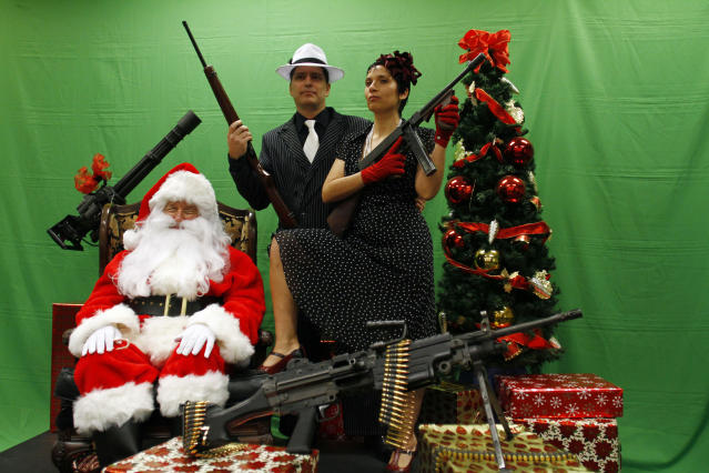 Todd Engle (C) and Mary Rose Engle (R) hold weapons as they pose for a photograph with a man dressed as Santa Claus at the Scottsdale Gun Club in Scottsdale, Arizona December 10, 2011. REUTERS/Joshua Lott (UNITED STATES - Tags: SOCIETY)