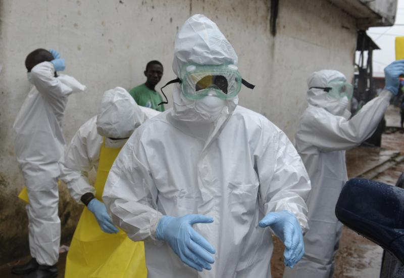 Health workers wearing protective clothing prepare to carry an abandoned dead body presenting with Ebola symptoms at Duwala market in Monrovia