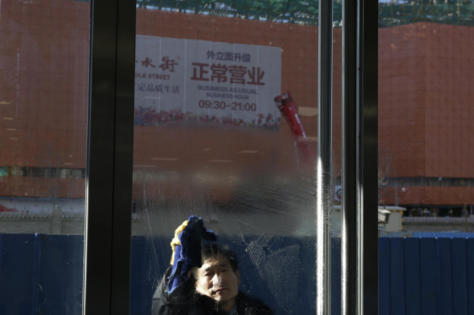 A man wipes a door panel against a shopping mall under renovation in Beijing, Tuesday, Jan. 15, 2019. China plans to slash taxes, step up spending and provide ample financing to private and small enterprises to help counter the country's worst slowdown since the global financial crisis and the impact of a bruising trade war with the U.S. (AP Photo/Andy Wong)