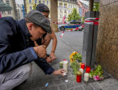 Flowers and candles are laid by young men at the crime scene in central Wuerzburg, Germany, Saturday, June 26, 2021. German police say several people have been killed and others injured in a knife attack in the southern city of Wuerzburg on Friday. (AP Photo/Michael Probst)