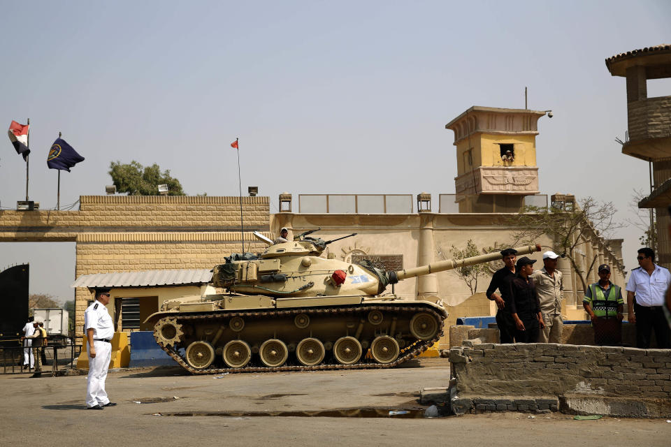 """FILE - In this Aug. 2, 2015 file photo, Egyptian security forces stand guard outside one of the entrances of Tora prison, in Cairo, Egypt. Since the coronavirus first hit Egypt in February 2020, At least 10 doctors and six journalists have been arrested according to rights groups. Other health workers say they have been warned by administrators to keep quiet or face punishment. One foreign correspondent has fled the country, fearing arrest, and another two have been summoned for reprimand over their reporting of """"disinformation"""" and other """"violations."""" (AP Photo/Hassan Ammar, File)"""