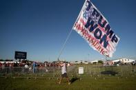 A man carries a flag that reads 'TRUMP WON' before a rally featuring former President Donald Trump Perry, Georgia (AFP/Sean Rayford)