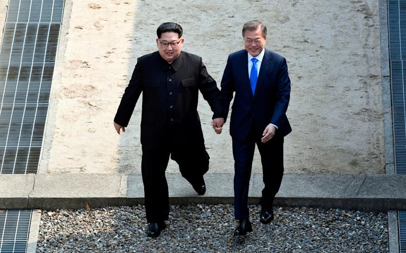 Kim Jong Un, left, and South Korean President Moon Jae-in cross the military demarcation line at the border village of Panmunjom in Demilitarized Zone on April 27, 2018 - Korea Summit Press Pool