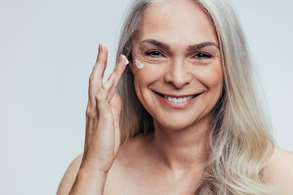 Smiling mid adult caucasian woman applying anti aging cream on her face. Senior female woman applying moisturizer on her face against grey background.