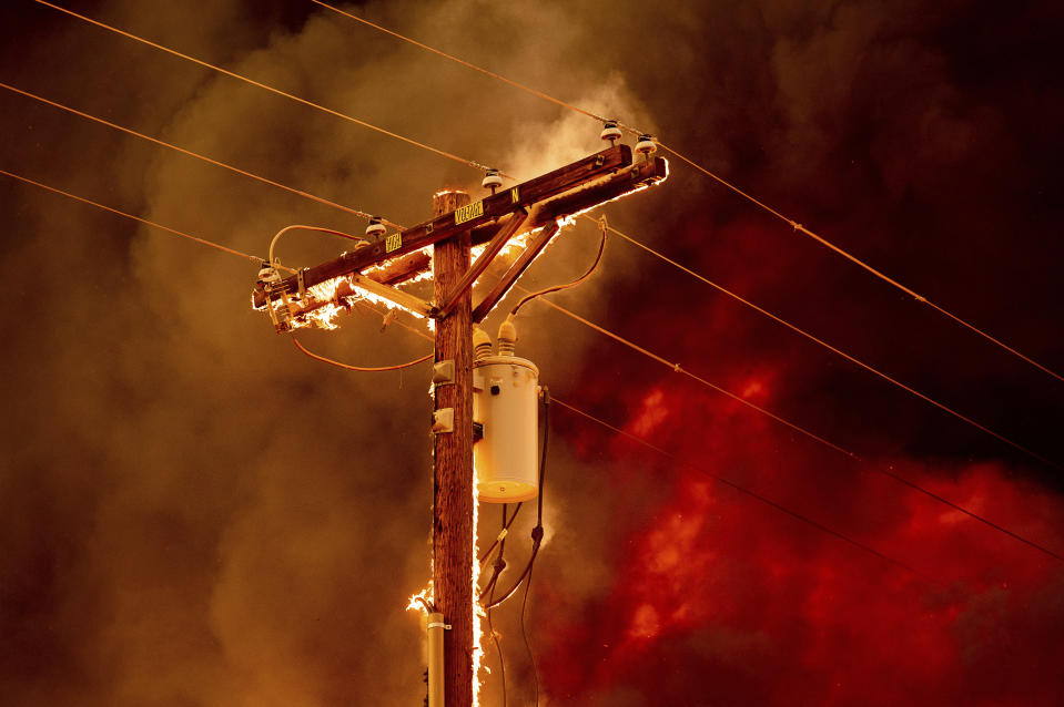 Fire burns along a power pole as the Sugar Fire, part of the Beckwourth Complex Fire, tears through central Doyle, Calif., on Saturday, July 10, 2021. (AP Photo/Noah Berger)