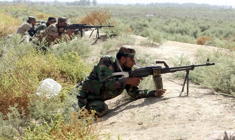 Shi'ite fighters from Saraya al-Salam take up positions during clashes with Islamic State militants in Jurf al-Sakhar
