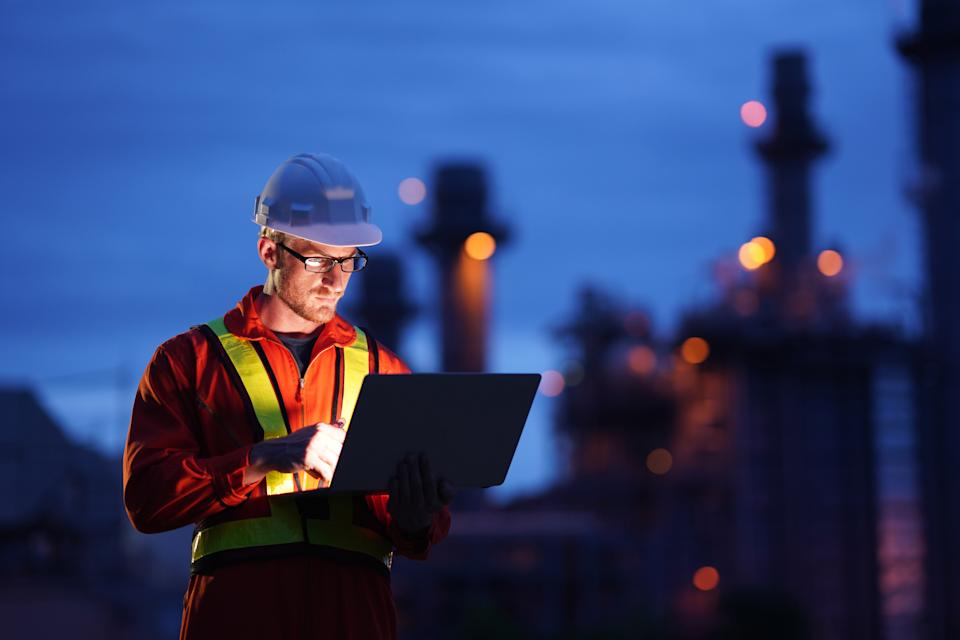 Engineer using laptop working while standing over Natural gas power Plant at construction site in evening twilling