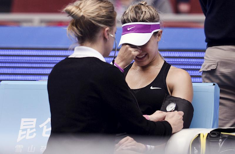 Bouchard of Canada is treated after she was injured while playing against Petkovic of Germany during their women's singles match at the China Open tennis tournament in Beijing