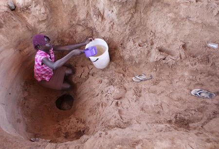 A woman fetches drinking water from a well along a dry Chemumvuri river near Gokwe, Zimbabwe, May 20, 2015. REUTERS/Philimon Bulawayo