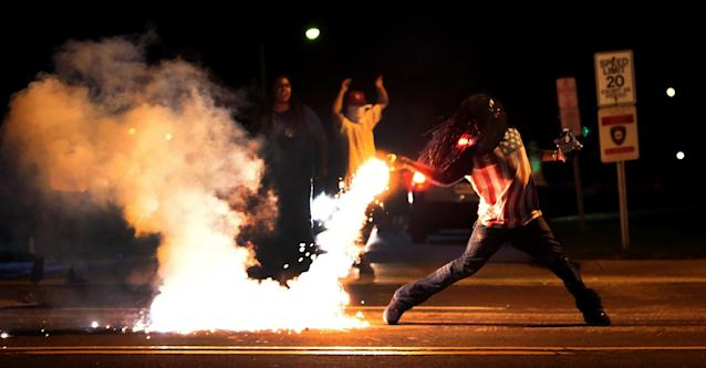 <p>Edward Crawford, returns a tear gas container shot by tactical police officers after they worked to break up a group of bystanders on Chambers Road near West Florissant on August 13, 2014 in Ferguson, Missouri. (Robert Cohen/St. Louis Post-Dispatch via ZUMA Press) </p>