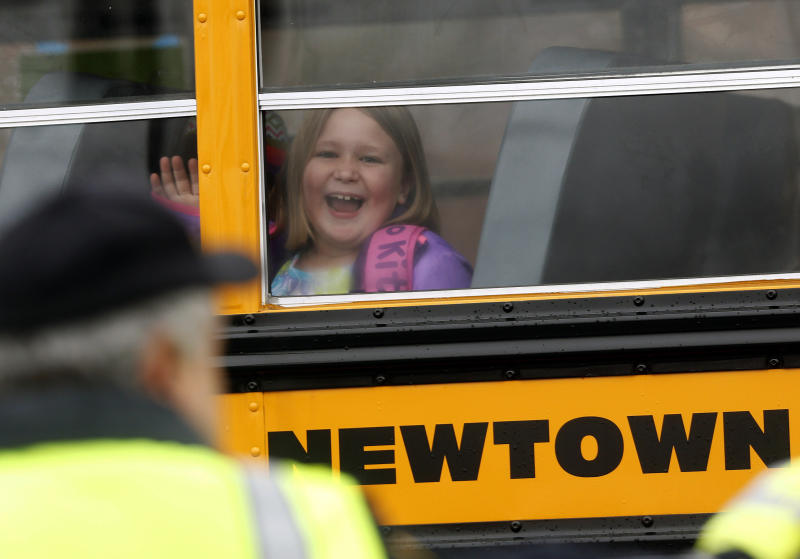 Classes resuming in Newtown, minus Sandy HookA young girl waves as her school bus pulls into Hawley School, Tuesday, Dec. 18, 2012, in Newtown, Conn.  Classes resume Tuesday for Newtown schools except those at Sandy Hook. Buses ferrying students to schools were festooned with large green and white ribbons on the front grills, the colors of Sandy Hook. At Newtown High School, students in sweatshirts and jackets, many wearing headphones, betrayed mixed emotions.  Adam Lanza walked into Sandy Hook Elementary School in Newtown,  Friday and opened fire, killing 26 people, including 20 children, before killing himself.(AP Photo/Jason DeCrow)