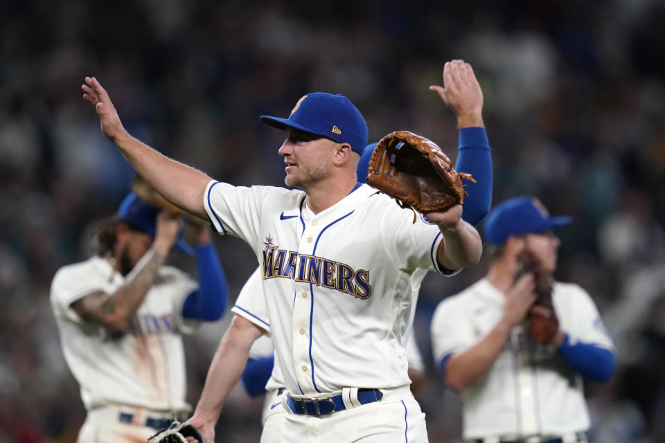 Seattle Mariners third baseman Kyle Seager waves to fans as teammates applaud behind as he leaves a baseball game against the Los Angeles Angels in the ninth inning Sunday, Oct. 3, 2021, in Seattle. (AP Photo/Elaine Thompson)